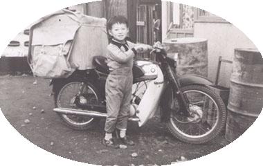 写真:創業当時の様子 集配用オートバイの前で